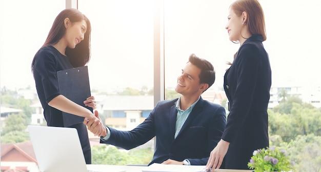 Gli uomini d'affari si stringono la mano e sorridendo il loro accordo per firmare il contratto alla riunione