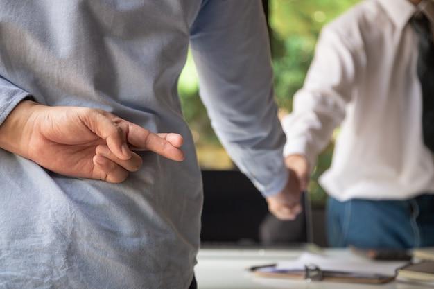 Gli uomini d'affari si stringono la mano e uno di loro tiene le dita incrociate dietro la schiena, rappresenta il tradimento.