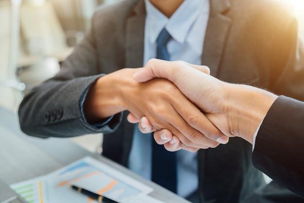 Gli uomini d'affari si stringono la mano, il partner finendo un incontro.