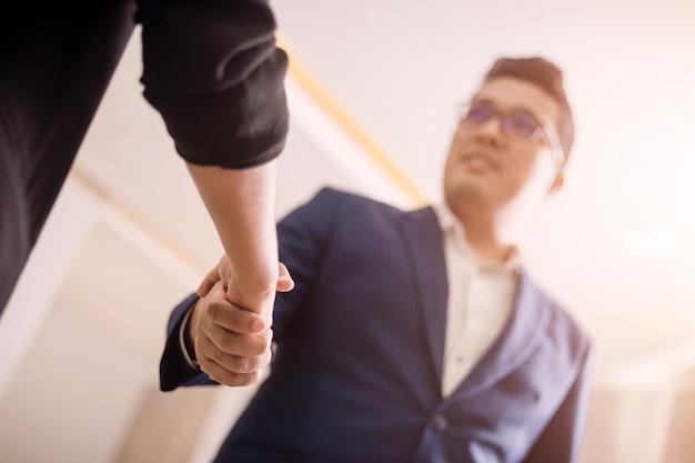 Gli uomini d'affari si stringono la mano, tra una riunione e l'altra nella stanza del seminario