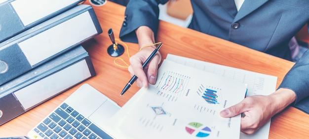 Gli uomini d'affari sono analizzati i dati dal rapporto utilizzando smartphone e laptop.