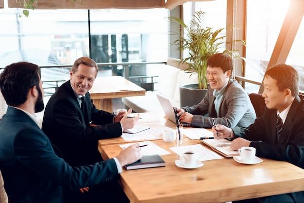 Gli uomini d'affari sono seduti dietro il tavolo.