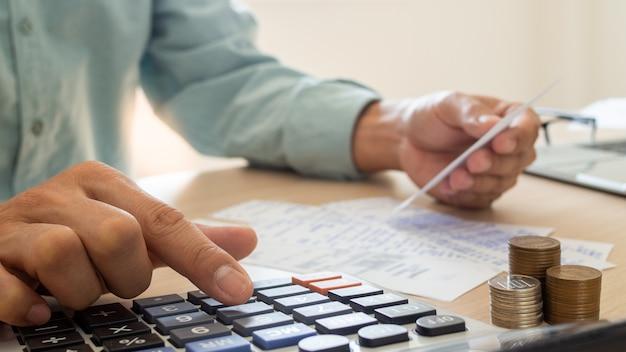 Gli uomini d'affari sono stressati per problemi finanziari, utilizzare un calcolatore per calcolare il costo delle entrate collocate sul tavolo. il concetto di debito