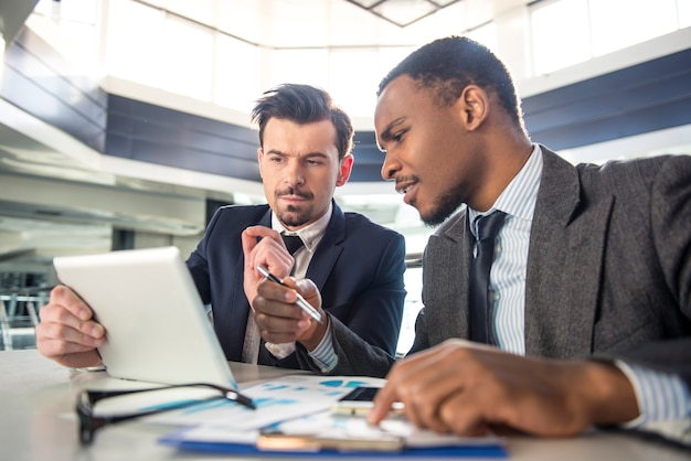 Gli uomini d'affari stanno lavorando con tablet pc in ufficio moderno.