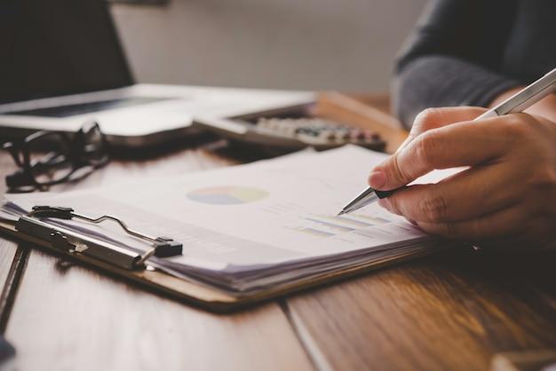Gli uomini d'affari stanno lavorando su conti in analisi di business con grafici e documentazione.