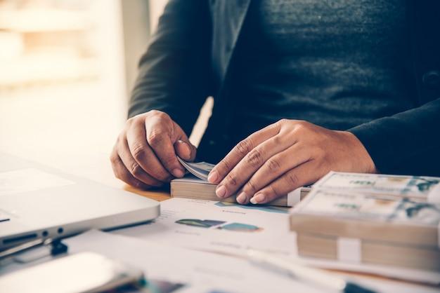 Gli uomini d'affari stanno lavorando sui dollari, calcolando profitti e guadagnando risultati,