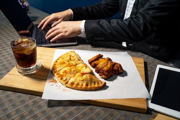 Gli uomini d'affari stanno mangiando pizza e cosce di pollo bbq sulla scrivania.