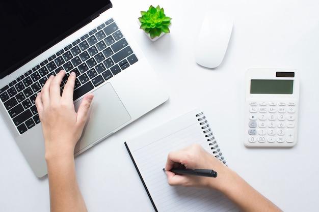 Gli uomini d'affari stanno prendendo appunti e utilizzando computer portatili su un tavolo bianco. concetto di contabilità, vista dall'alto.
