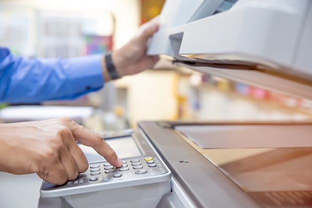 Gli uomini d'affari stanno usando la fotocopiatrice.