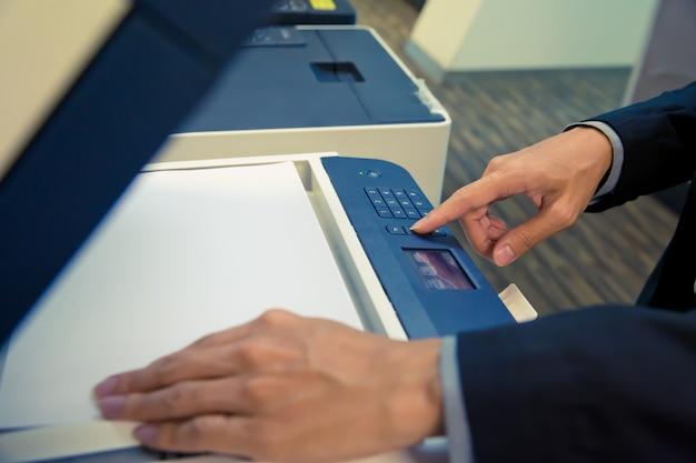 Gli uomini d'affari stanno usando le fotocopiatrici.