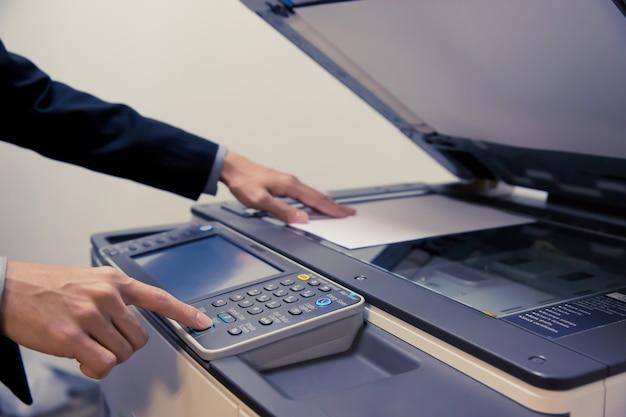 Gli uomini d'affari stanno usando le fotocopiatrici