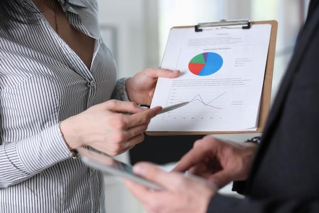 Gli uomini d'affari studiano i documenti in ufficio. discutere il rapporto del grafico