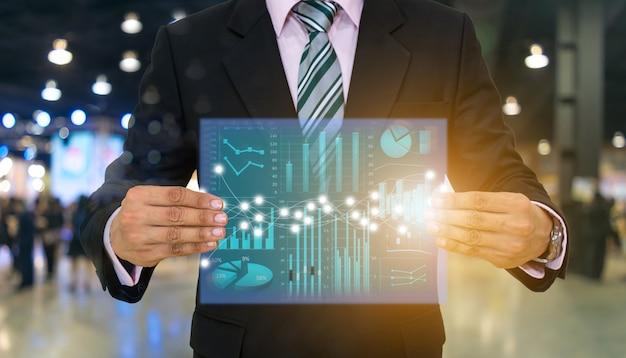 Gli uomini d'affari tengono lo schermo e la tecnologia finanziaria dei grafici di investimento