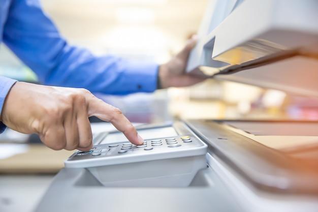Gli uomini d'affari utilizzano fotocopiatrici, scansionano documenti in ufficio.