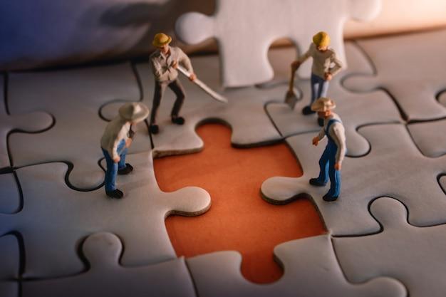 Gli uomini dei lavoratori in miniatura hanno riscontrato un errore nel puzzle