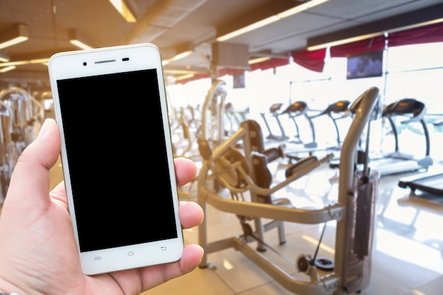 Gli uomini del primo piano usano la mano che tiene le immagini vaghe dello smartphone della sfuocatura astratta dello spor defocused