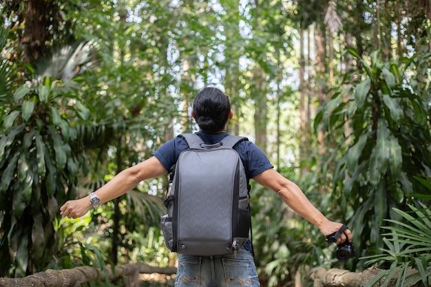 Gli uomini del viaggiatore di libertà che stanno con le armi alzate e che godono di bella natura e che incoraggiano i giovani al tramonto, si rilassano il tempo sul viaggio di concetto di vacanza