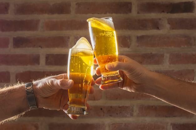 Gli uomini di vista frontale esultano con un bicchiere di birra