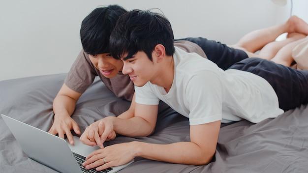 Gli uomini gay asiatici del lgbtq si accoppiano facendo uso del computer portatile del computer a casa moderna. il giovane maschio dell'amante dell'asia felice si rilassa insieme dopo il risveglio, guardando il film che si trova sul letto in camera da letto a casa di mattina.