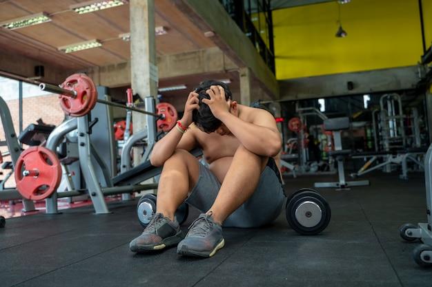 Gli uomini grassi sono preoccupati, l'uomo grasso seduto sul pavimento dopo l'allenamento in palestra.