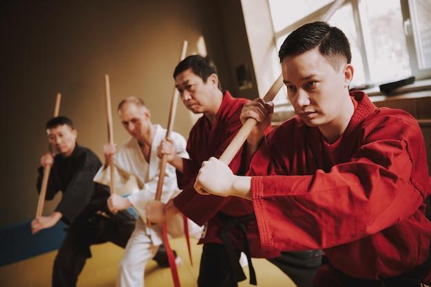Gli uomini in allenamento praticano metodi con bastoncini.