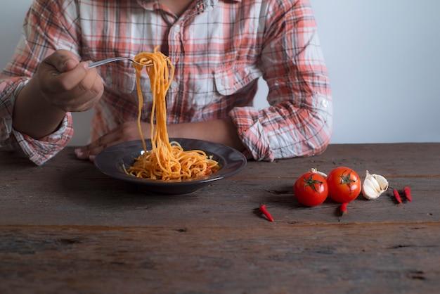 Gli uomini indossano le camicie tenendo in mano uno spaghetti con un cucchiaio. appoggiati su un tavolo di legno