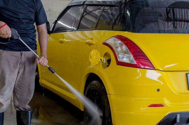 Gli uomini lavano l'autolavaggio