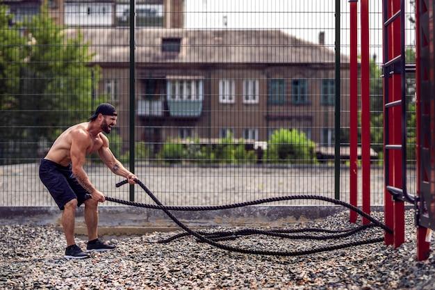 Gli uomini lavorano duramente con la corda, allenamento funzionale