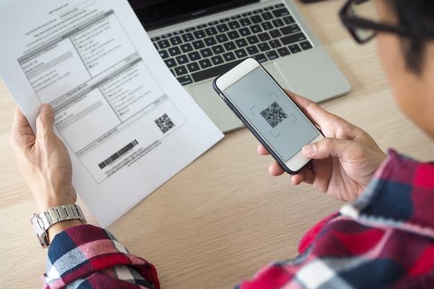Gli uomini pagano i soldi dell'assicurazione sulla vita annuale tramite applicazioni bancarie via telefono.