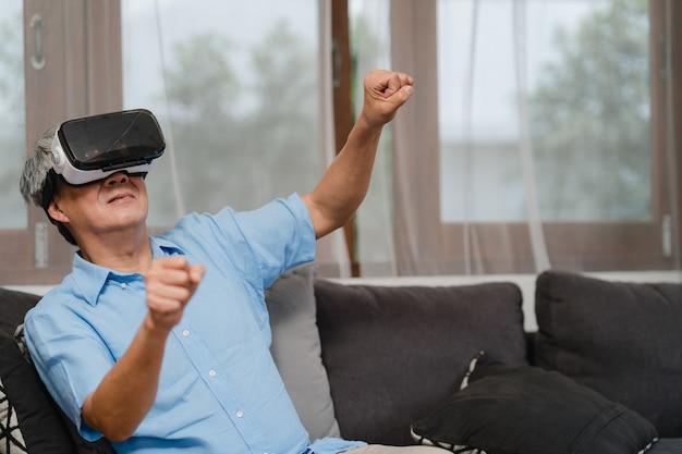 Gli uomini senior asiatici giocano a casa. divertimento felice maschio cinese senior senior asiatico e realtà virtuale, vr che gioca mentre sofà di menzogne nel concetto del salone a casa.
