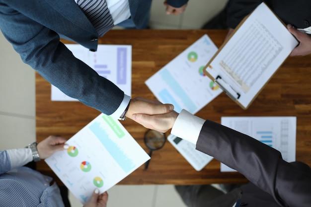 Gli uomini si stringono la mano sul tavolo con dei rapporti.