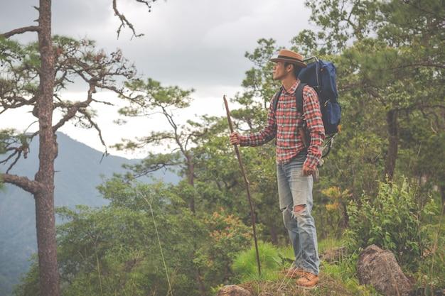 Gli uomini stanno a guardare le montagne nelle foreste tropicali con gli zaini nella foresta. avventura, viaggi, arrampicata.