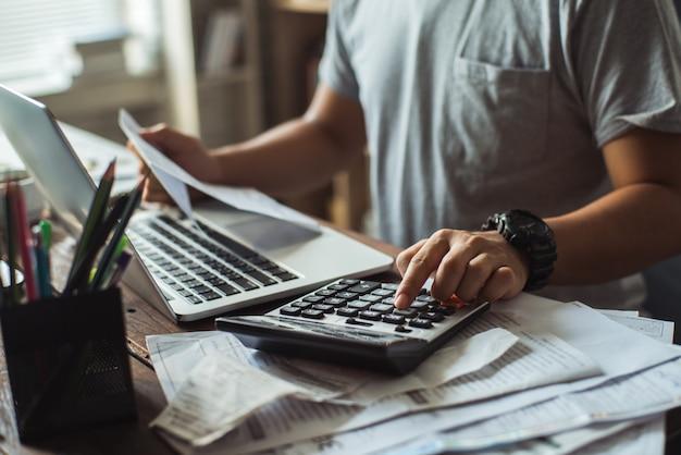 Gli uomini stanno calcolando il costo del conto. sta premendo il calcolatore.