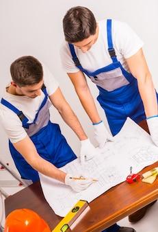 Gli uomini stanno in piedi e pianificano il piano di costruzione.