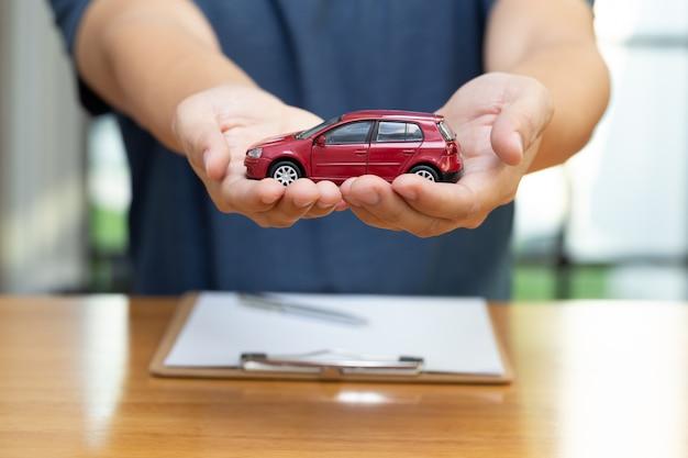 Gli uomini stanno scegliendo di acquistare e firmare la polizza di contratto con l'assicurazione del veicolo e dell'automobile, protezione del concetto dell'automobile