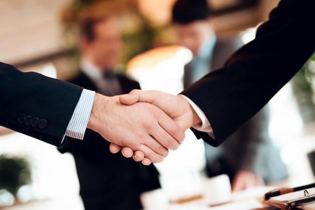 Gli uomini stanno stringendo la mano.