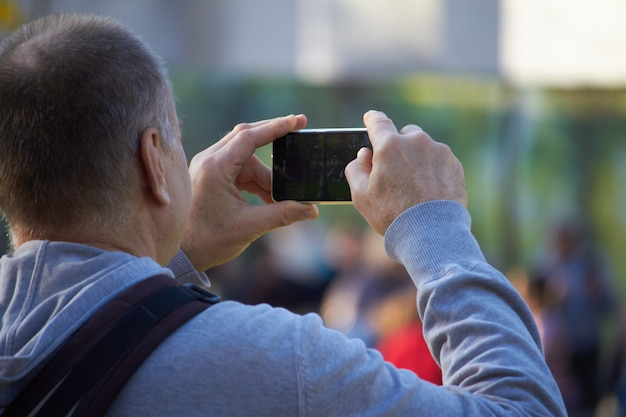 Gli uomini sulla strada fotografare con il cellulare, lo sfondo è città blured
