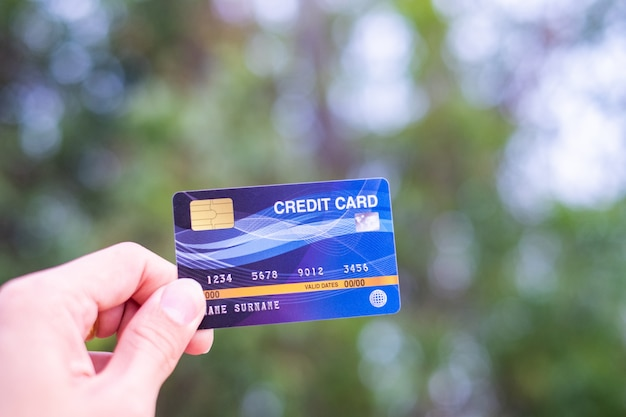Gli uomini tengono la carta di credito sulla natura del bokeh
