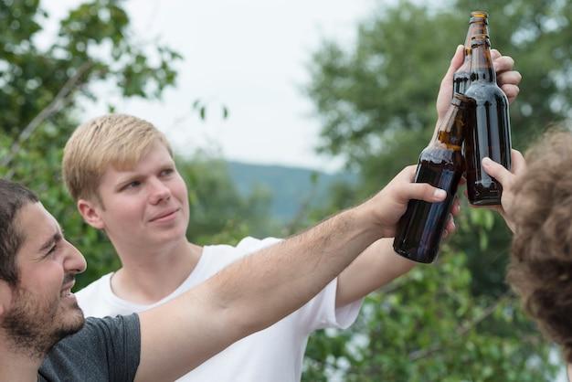 Gli uomini tintinnano le bottiglie in campagna