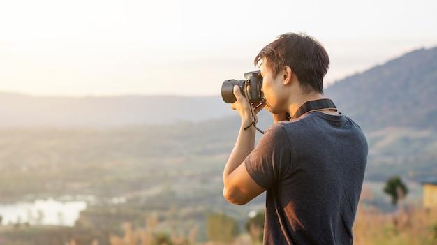 Gli uomini viaggiano e scattare una foto del tramonto sulla montagna.