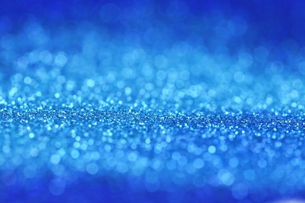 Glitter sfondo blu con luce blu brillante bokeh.