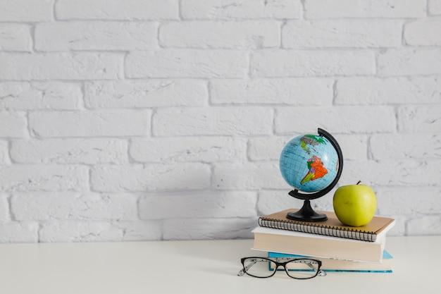 Globo del mondo, libri, mela e bicchieri
