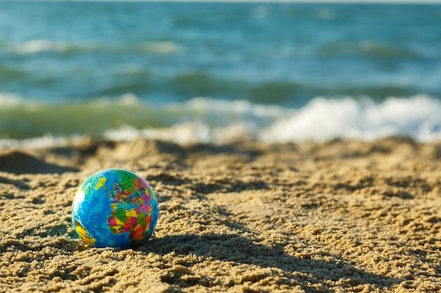 Globo del pianeta terra su una spiaggia di sabbia su uno sfondo di oceano. viaggia intorno al concetto del mondo.