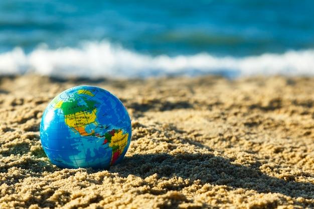 Globo del pianeta terra su una spiaggia di sabbia su uno sfondo di oceano.