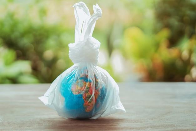 Globo di concetto di giornata per la terra nel sacchetto di plastica sulla tavola