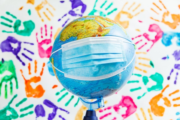 Globo in una mascherina medica protettiva sullo sfondo di impronte di mani colorate.