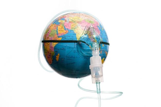 Globo terrestre con una maschera per inalatore, isolato su uno sfondo bianco. pericolo di epidemia umana.