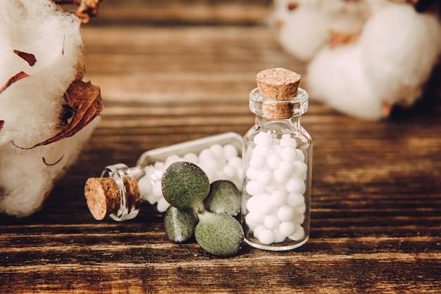 Globuli omeopatici e fine della bottiglia di vetro su su superficie di legno.