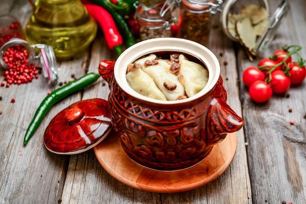 Gnocchi con carne e patate in una pentola di terracotta