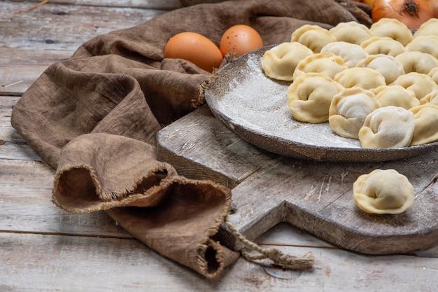 Gnocchi crudi di carne - pelmeni russo sul tagliere